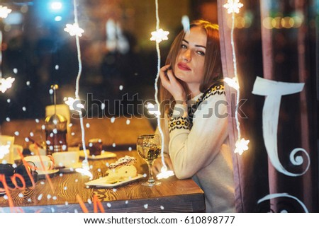 Young beautiful woman sitting in cafe, drinking wine. Magic snowfall effect. Christmas, new year, Valentines day, winter holidays concept. The photo was taken through the window