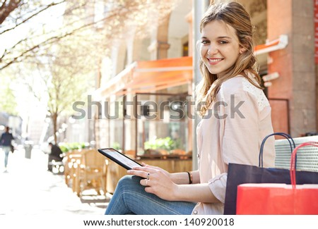 Young beautiful woman sitting on a bench in a city center during a sunny day, using a digital tablet pad near a classic building with arches, smiling. - stock photo