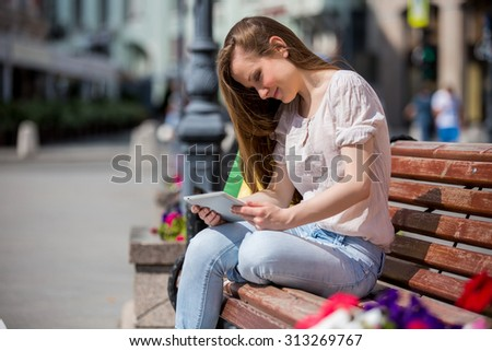 Young beautiful woman sitting on a bench with digital tablet next to the shopping bags. Relaxing and using the device with happy smile