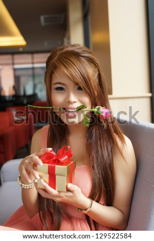 Young beautiful woman sitting on a couch while opening a gift box. - stock photo