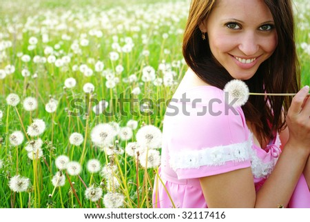 Young beautiful woman sitting on a green grass with dandelions - stock photo