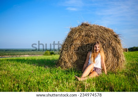 young beautiful woman sitting on a green meadow against a haystack