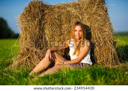 young beautiful woman sitting on a green meadow at sunset on the background of haystacks - stock photo