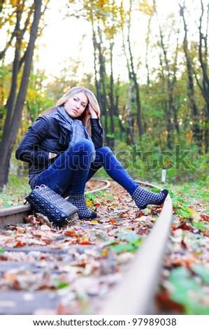 Young beautiful woman sitting on a railroad - stock photo