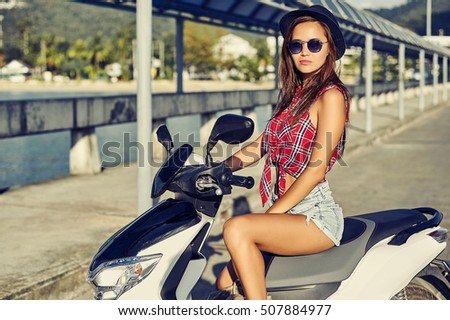 Young beautiful woman sitting on a scooter