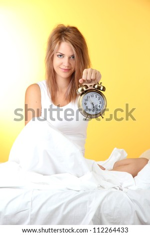 young beautiful woman sitting on bed with alarm clock on yellow background