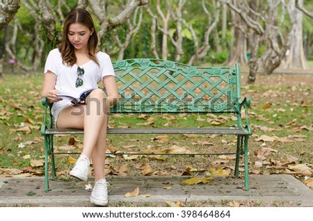 Young beautiful woman sitting on bench and reading book in park. Pretty girl at outdoors on summer day. Nature environment background. - stock photo