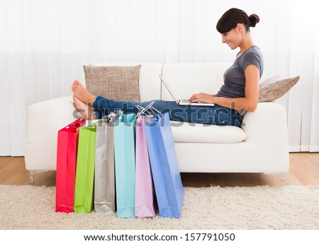 Young Beautiful Woman Sitting On Couch Shopping Online - stock photo