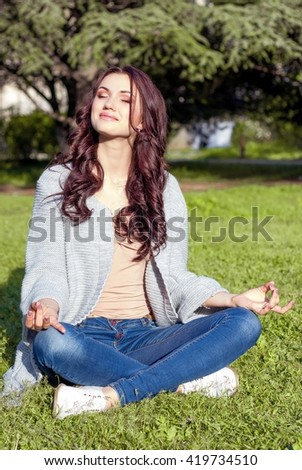 Young beautiful woman sitting on green grass in the park. A warm sunny day. Young happy woman. Young woman relaxes in the park.