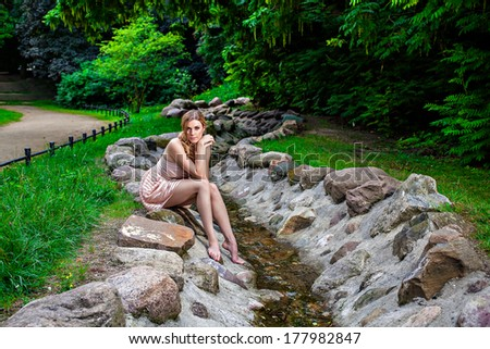 Young beautiful woman sitting on rock by stream in park