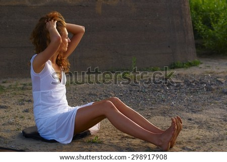 Young beautiful woman sitting on sand of beach