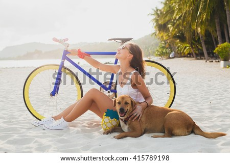 young beautiful woman sitting on sand on beach, holding vintage bicycle, hugging dog, happy mood, smiling, hipster casual outfit, sunglasses, slim body, summer vacation, relaxed - stock photo