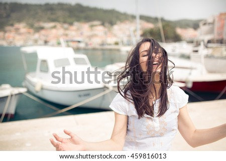 Young beautiful woman sitting on seaside and meditating . Finding your inner peace. Meditation on Mediterranean Sea. Girl enjoying her earned vacation.Relaxation and leisure concept