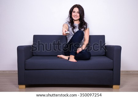 young beautiful woman sitting on sofa and watching tv at home - stock photo