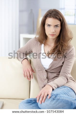 Young beautiful woman sitting on sofa at home in living room.
