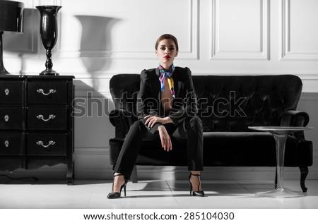 young beautiful woman sitting on sofa in minimalistic inteior - stock photo