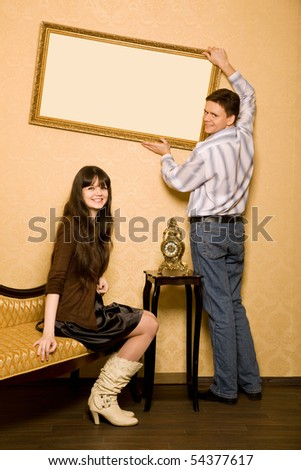young beautiful woman sitting on sofa in room and smiling man hang up on wall picture in frame - stock photo