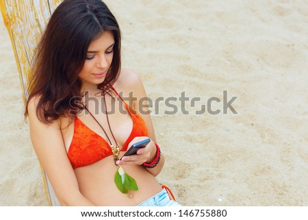Young beautiful woman sitting on the beach with her smartphone - stock photo