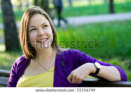 young beautiful woman sitting on the bench in park and listening music
