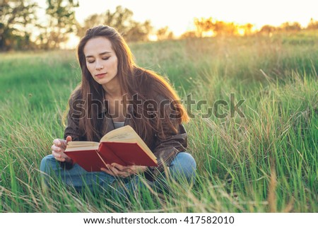 Young beautiful woman sitting on the grass and reading a book