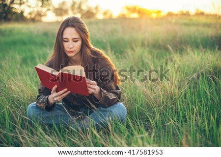 Young beautiful woman sitting on the grass and reading a book. Sunset
