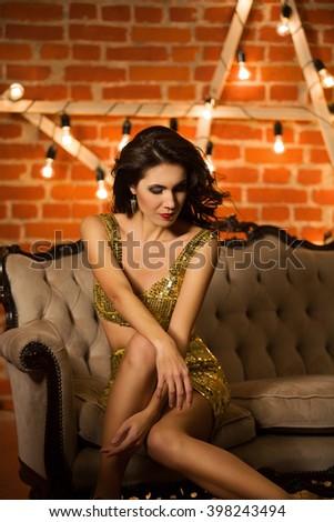 Young beautiful woman sitting on the sofa - stock photo