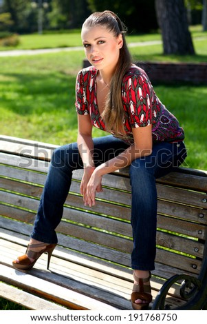 Young beautiful woman sitting on the wood bench - stock photo