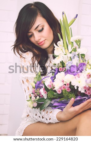 Young beautiful woman sitting on window sill with flowers