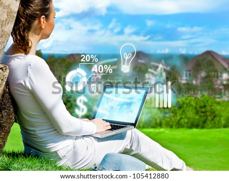 Young beautiful woman sitting under a tree and working with her laptop by internet. Freelance and internet business concept - stock photo