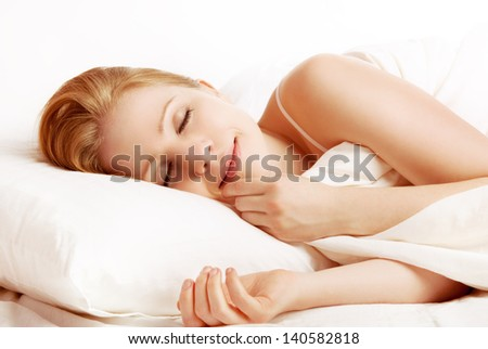 young beautiful woman sleeping and smiles in his sleep in  bed - stock photo
