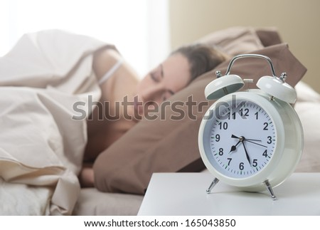 Young beautiful woman sleeping comfortably on bed - stock photo