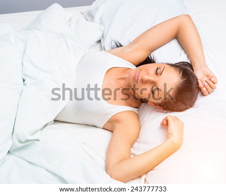 young beautiful woman sleeping in white bed at home