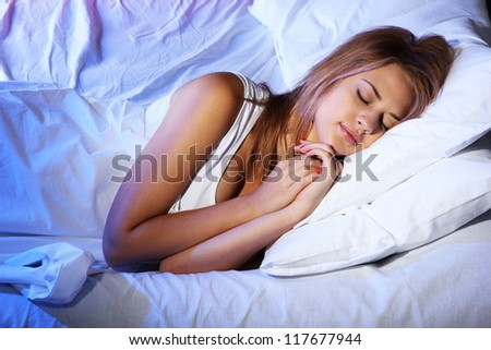 young beautiful woman sleeping on bed in bedroom - stock photo