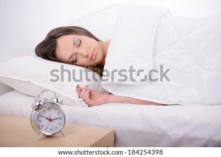 Young beautiful woman sleeping on bed with alarm clock in bedroom - stock photo