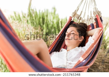 Young beautiful woman sleeping on hammock in the very hot summer day on the beach or desert. Moment from the vocation. Tired from the trip. - stock photo