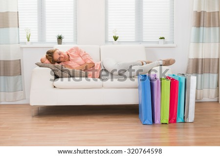 Young Beautiful Woman Sleeping On Sofa With Shopping Bags On Floor - stock photo