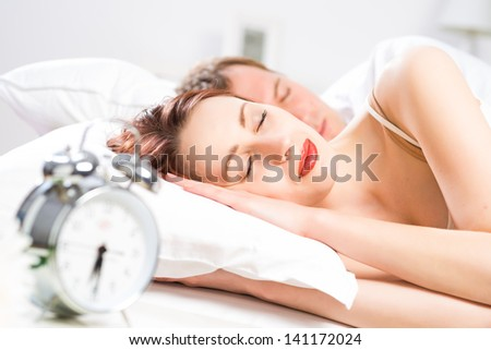 young beautiful woman sleeping on the bed with her husband - stock photo
