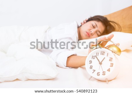 Young beautiful woman sleeping with alarm clock
