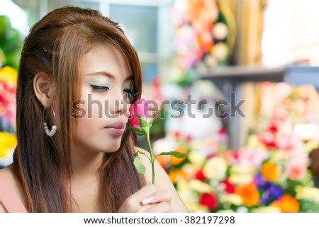 Young beautiful woman smelling rose with blurred flower shop background - stock photo