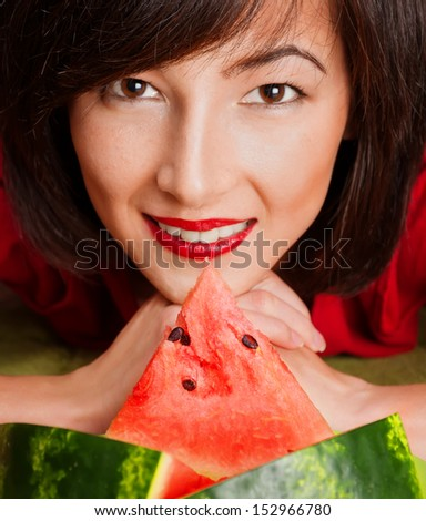 Young beautiful woman smiling, in front of her a plate of watermelon - stock photo