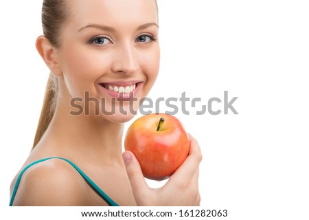 Young beautiful woman smiling on camera. Holding beautiful apple