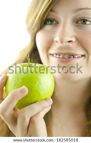 Young beautiful woman smiling with braces holding a green tasty apple isolated on white background