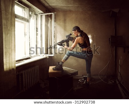 Young beautiful woman sniper and Soldier aiming a rifle at the window. She is in old room of abandoned building - stock photo