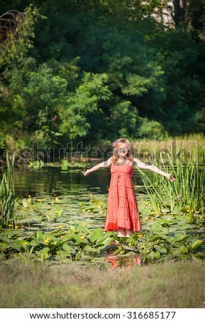 young beautiful woman spread her arms while standing in water
