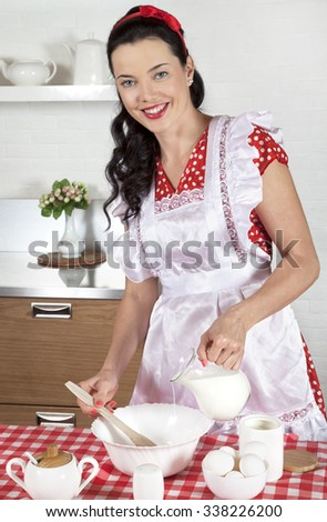 Young beautiful woman standing by the table in the kitchen, cooking the meal - stock photo