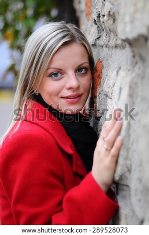 young beautiful woman standing near a stone wall in a red coat at the autumn park
