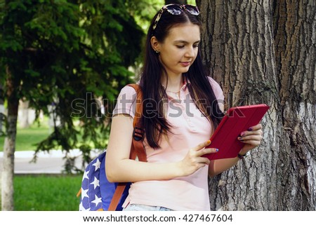 young beautiful woman standing near a tree on the grass in the park and use the app in your comuter tablet