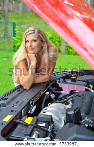 Young beautiful woman standing near red car and looking under hood on the engine and other car details