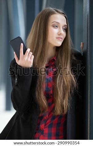 Young beautiful woman standing near the window and holding her mobile phone. - stock photo