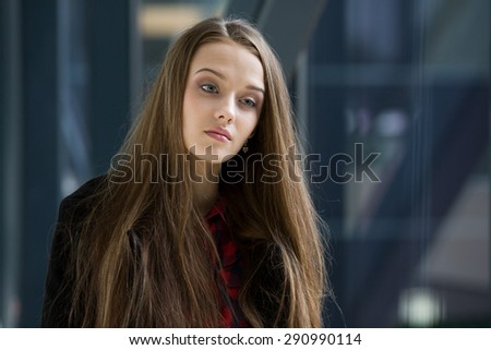 Young beautiful woman standing near the window and thinking. - stock photo